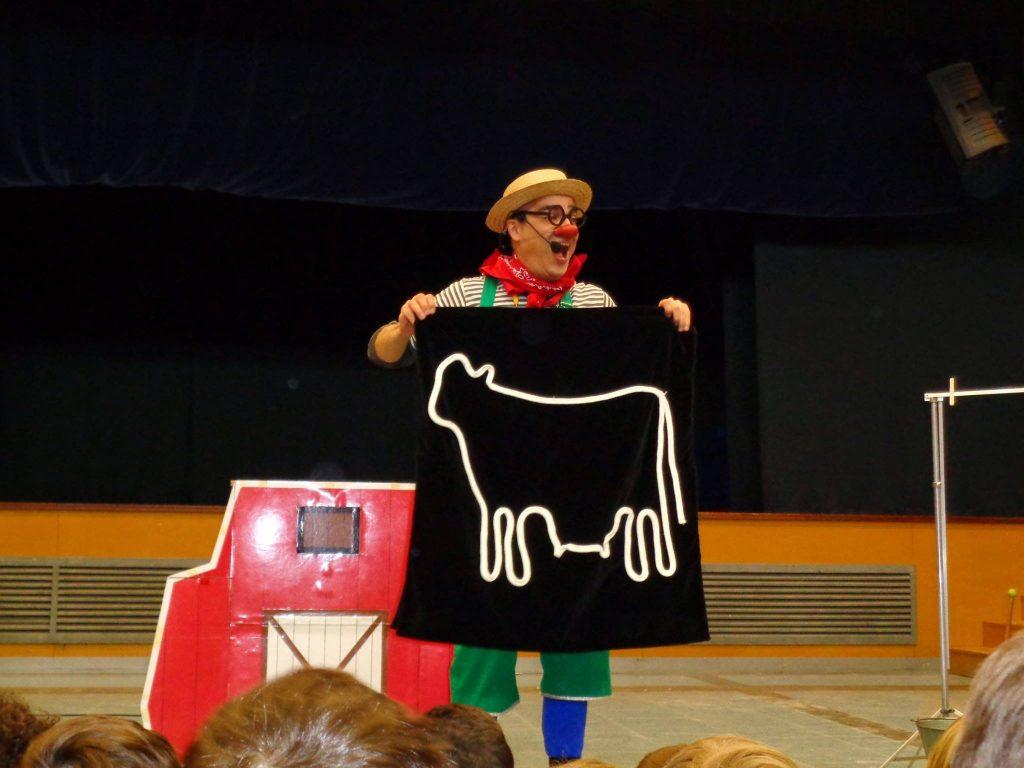 Escena de l'obra Let's Go to the Farm en què Ruskus Patruskus ensenya la silueta d'una vaca sobre un fons negre